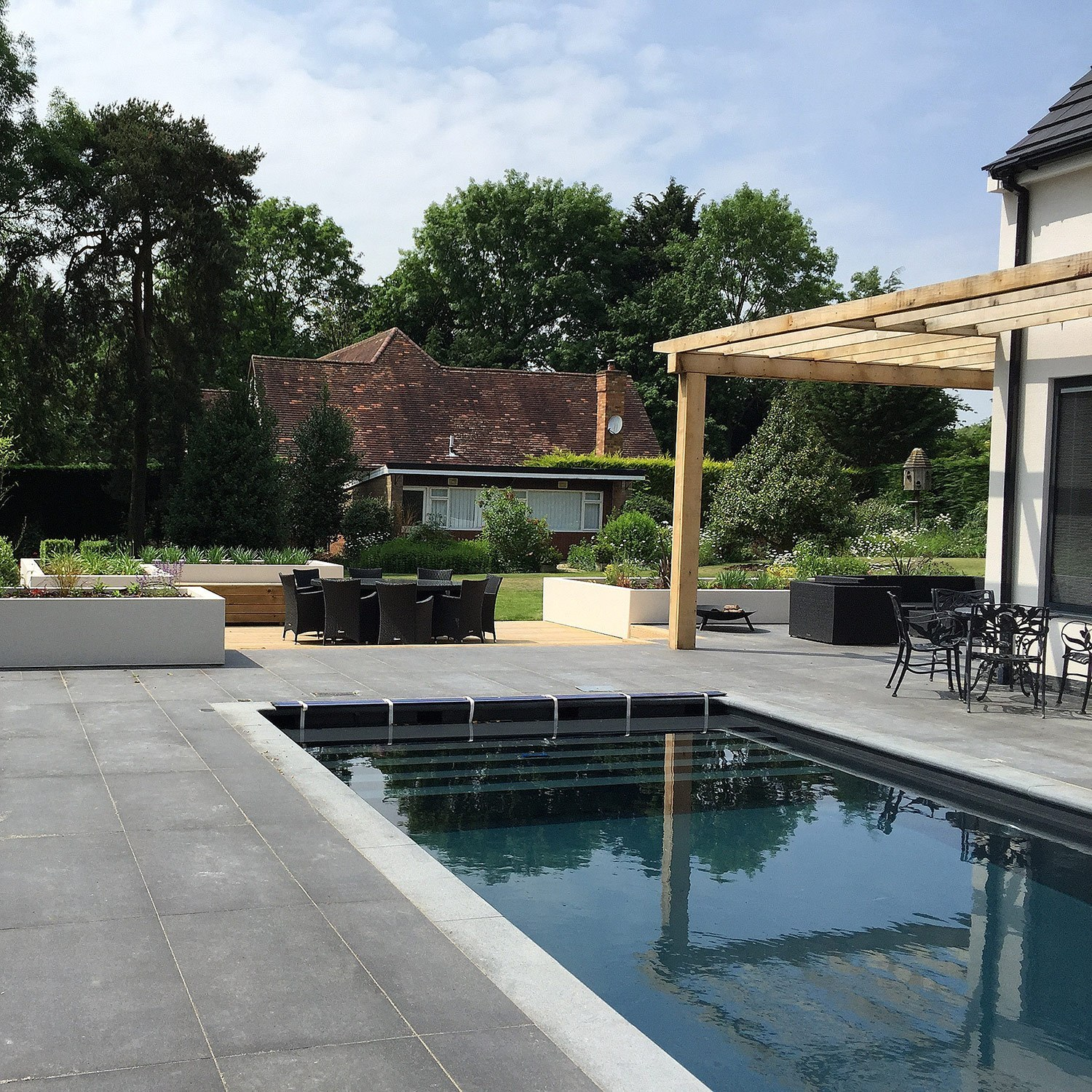 Swimming pool with large patio and pergola